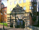Zamek w Oleśnicy - brbakan z ozdobną bramą, w tle pałac wdów